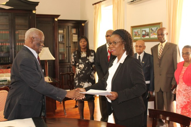 Governor General Sir Elliott Belgrave (left) shaking the hand of newly appointed Justice Pamela Beckles (right) as her family members (from left) Beverly Beckles; sister, Anderson Sandiford; cousin, and family friend Astor B Watts look on.