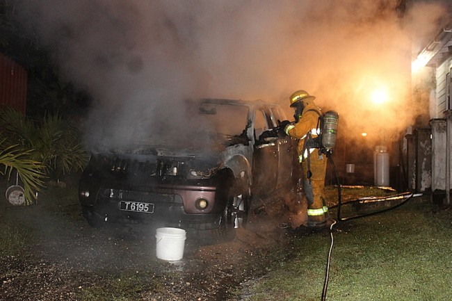 A fire officer tending to the burnt out vehicle owned by West Indies international cricketer Jonathan Carter.