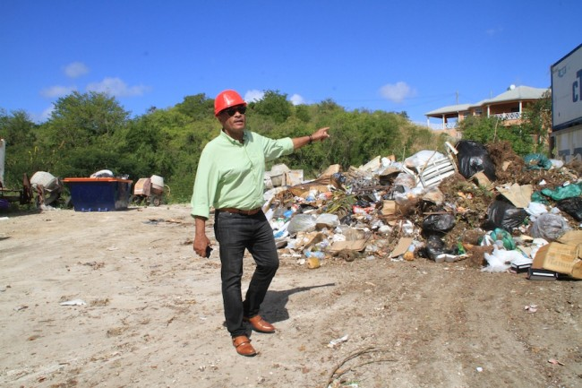Former Minister of Transport and Works Rommell Marshall identifies some of the garbage dumped at Robinson Close, St Stephen's.