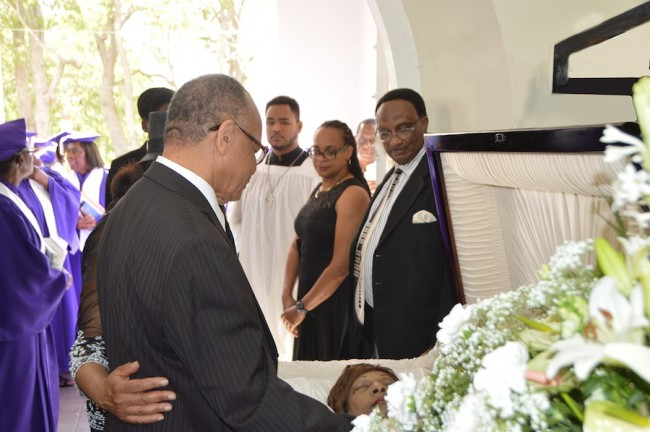 Jean Holder takes a last look at his wife of 54 years before the funeral service began. His brother-in-law Winston Edmondson and his daughter Caroline Holder-DeLaCour look on.