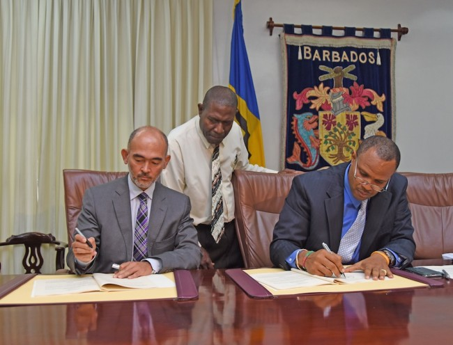 Minister of Finance Chris Sinckler and IDB's Country Representative Juan Carlos de la Hoz, signing the agreement, while Manager of the Public Investment Unit Seibert Frederick looks on.