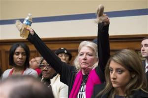 Flint, Michigan resident Glaydes Williamson holding up water from Flint and hair pulled from her drain, during the House Oversight and Government Reform Committee hearing to examine the ongoing situation in Flint, on Capitol Hill in Washington.