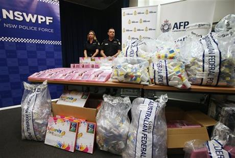 Officers standing by a display of confiscated drugs in Sydney today.