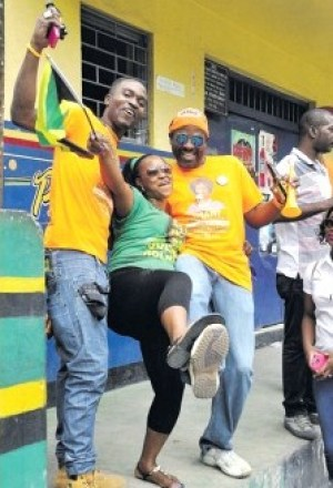 People's National Party supporters having fun with a Jamaica Labour Party supporter on nomination day in a show of friendly rivalry.