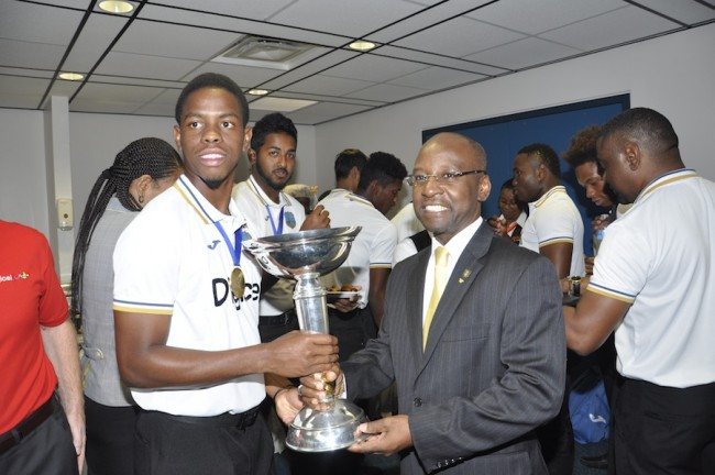 West Indies captain Shimron Hetmyer (left) pose with the trophy with Minister of Sports Stephen Lashley, while other members of the team sample some of the fare provided for them.