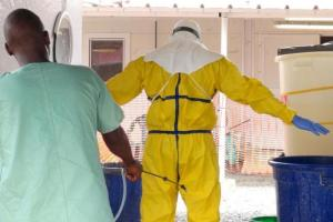 A health worker getting sprayed with disinfectant in an Ebola virus treatment centre in Conakry, Guinea, November 17, 2015.