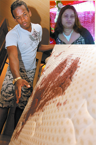 Adam Soodeen, the nephew of Jennifer Rampersad (inset), shows her blood-stained mattress at the family's New Grant home yesterday.