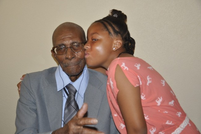 The birthday boy receiving a kiss from his great granddaughter Thia Agard.