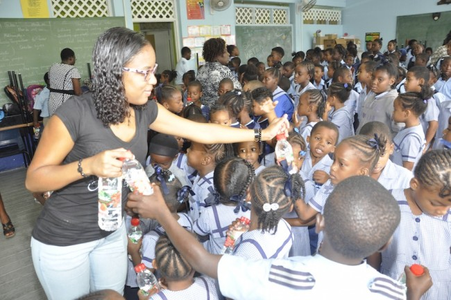 Account Executive Tamesha Doughty distributing Volvic  bottled water, donated  by Massy Distribution,  to the students.