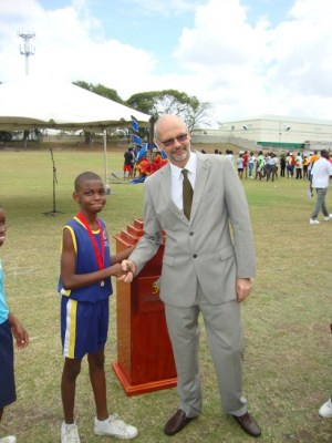 Deshawn Maynard receives his bronze medal for the Division 17 200m from Ambassador Mikael Barford.