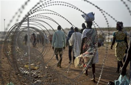 Displaced people walking next to a razor wire fence at the United Nations base in the capital Juba, South Sudan.