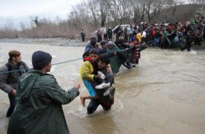 Migrants wading across a river near the Greek-Macedonian border, west of the the village of Idomeni, Greece, today.