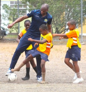 Captain of the Barbados senior men's team Emmerson Boyce having some fun with the kids today at Deacons.