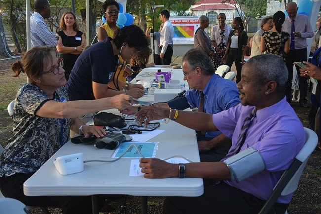 Health officials, including Acting Chief Medical Officer Dr Kenneth George (right), joined members of the pubic in getting health checks at PAHO's launch of the Global Report on Diabetes.