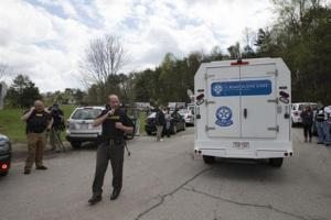 Authorities allow crime scene investigation vehicles to pass a perimeter checkpoint near a crime scene on Friday, in Pike County, Ohio.