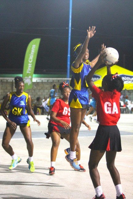 Barbados' goal-defence Chante Moore jumps high to block Trinidad and Tobago goal-attack Kadeemah Herbert.