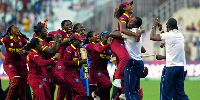 Carlos Brathwaite lifts Hayley Matthews in the air as the West Indies men's team join the women's celebrations.