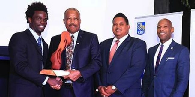 Chadwick Walton, (left) receives his Sportsman of the Year award from UWI Vice-Chancellor, Professor Sir Hilary Beckles at the Daaga Auditorium at The UWI St Augustine campus. Sports Minister Darryl Smith (right) looks on.