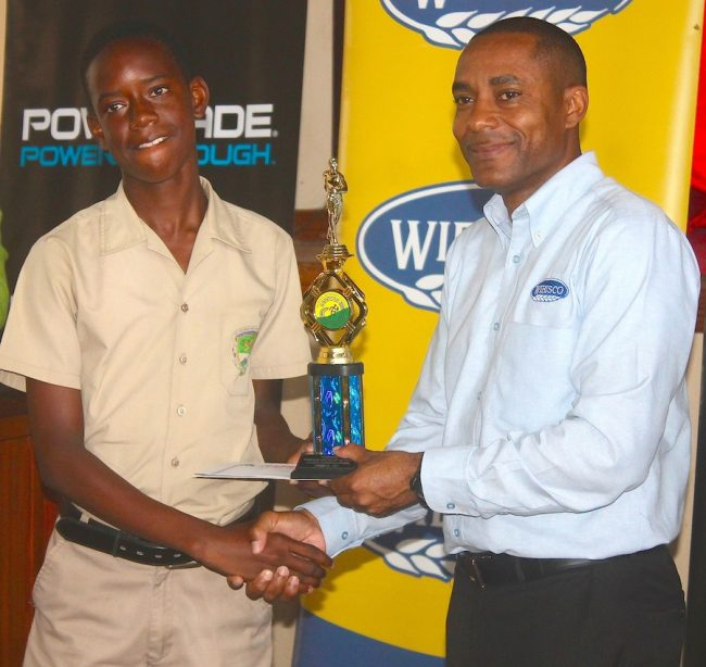 Jamarco Gill (left) of St George Secondary was named under-13 division champion and collects his award from Clifford Gooding- Edghill, category manager of WIBISCO.