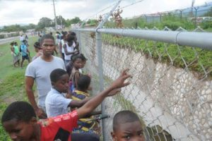 Residents of the Stadium Gardens and neighbouring Swallowfield communities gather along the perimeter fence of the gully bank behind the National Indoor Sports Centre where the body of what appeared to be a newborn child was found Sunday afternoon.