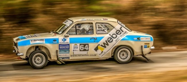 The blue and white Ford Escort MkI with Ray Clough at the wheel.