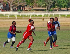 Trinidad and Tobago All Star Chantelle Charles (with ball) breaking away from Barbadians Gloria Lwegaba (left) and Ayodele Edinboro (right).