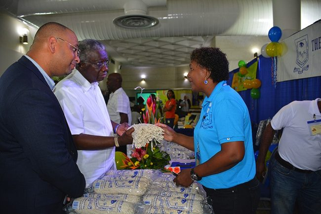 Blind and Deaf Association member Cheryl Griffith  showing Prime Minister Freundel Stuart one of the superior mops. At left is BMA President Jason Sambrano.