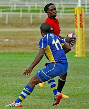 Agboola Silverthorne (Trinidad & Tobago) evades Barbados' Dario Stoute on his way to another try.