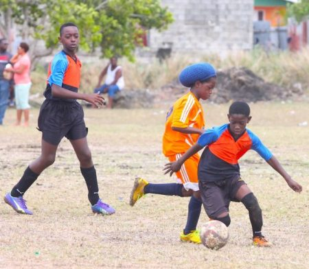 Amego Jordan of Wilkie Cumberbatch dribbles around Meshach Beckles from Belmont Primary.