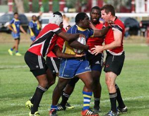 "Bajan hooker Jeren ""Blinki"" Clarke attempts to retain possession of the ball against a swarm of red Trinidadian jerseys."
