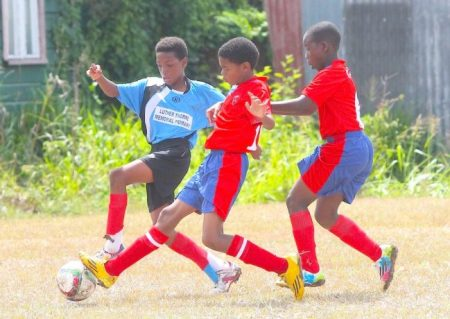 Charles F. Broome's goal-scorer Yanic Marshall (center) gets to the ball before Ty-dre Fenty of Luther Thorne Primary.