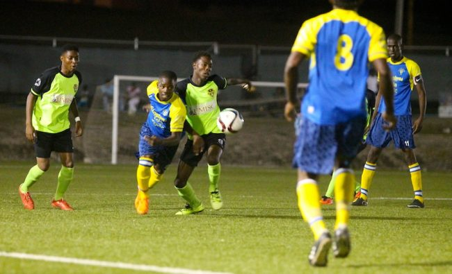 Clayton's Kola Tonic Notre Dame striker Antone Greaves does well to out-pace Solaris Pinelands defence while goal-scorer Kyle Gibson (right) looks on.
