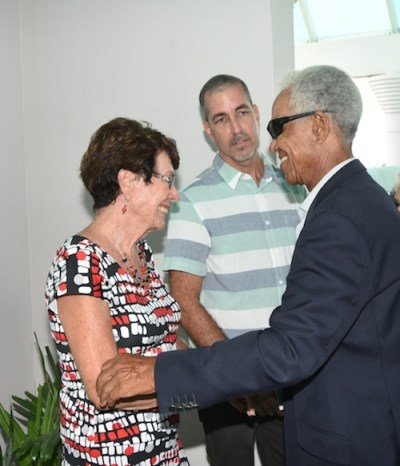 Cricket legend and National Hero Sir Garfield Sobers greets Jillian Cozier, widow of the late Tony Cozier, as Cozier's son Craig looks on.