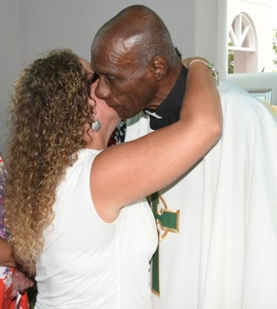 Cricket legend and Reverend Sir Wes Hall greets Tony Cozier's daughter Natalie.