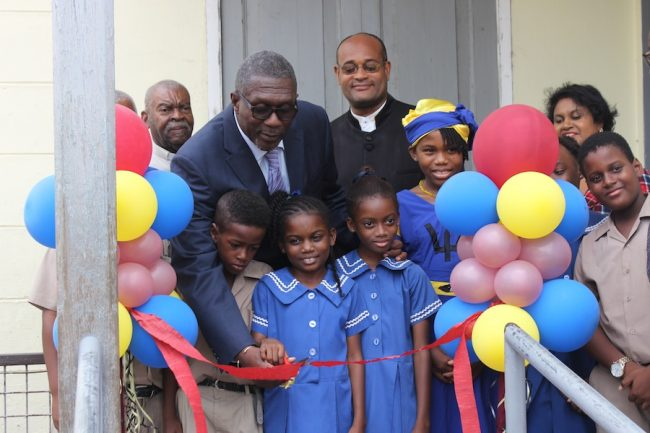 Parliamentary Secretary in the Ministry of Education Senator Harcourt Husband (left at back) former Member of Parliament for the City Patrick Todd (right at back) cutting the ribbon with students of the Wesley Hall Junior School to open the school's first career showcase.
