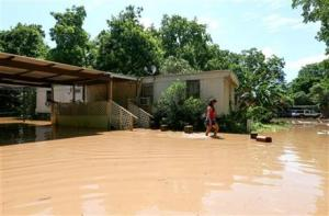 Irene Martinez, who lives near the Brazos River, leaves her flooded home Sunday in Richmond, Texas.