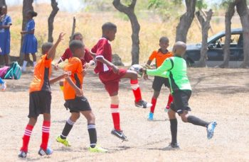 Kadari Webster of Hilda Skeene Primary challenges Blackman and Gollop Primary's goal-keeper Atori Holder for the ball.