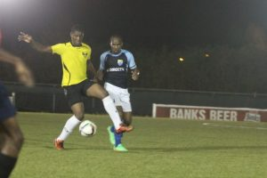 University of the West Indies Blackbirds striker Diquan Adamson takes control of the ball under challenge from Steven Griffith of Direct TV Paradise.