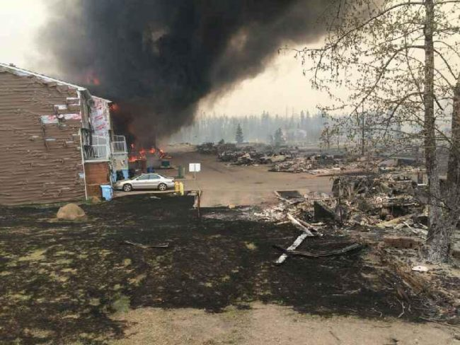 Smoke rises in a burned-out neighborhood in Fort McMurray, Alberta, May 6, 2016, after wildfires forced the mass evacuations of the areas around Fort McMurray. Bonnyville Regional Fire Authority (BRFA)/Handout via Reuters