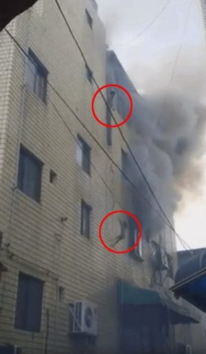 A screenshot from video taken at the scene of the fire as one child drops to safety.