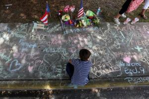 A child draws on the sidewalk in chalk at a makeshift memorial that is across the street from Pulse night club following last week's shooting in Orlando, Florida.