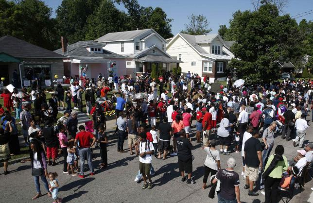 Mourners gather outside Muhammad Ali's childhood home during the funeral procession for the three-time heavyweight boxing champion in Louisville, Kentucky, U.S., June 10, 2016.  REUTERS/Lucy Nicholson