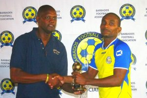 Barbados Football Association first vice-president Captain Al Walcott (left) presents Romano Snagg of Rendezvous with his Most Valuable Player award.