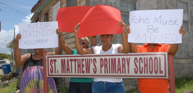 Concerned parents of St Matthew's Primary holding placards demonstrating their frustration with principal of the school.
