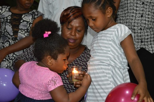Daughter of murder victim Kimberly Lovell, three-year-old Danea (left) attempting to blow out a candle at a vigil held at the Queen Elizabeth Hospital where her mother was a critical care nurse in the recovery unit.  Looking on is Danea's sibling five-year-old Danae (right) and their grandmother Cicely Sargeant who has promised  to embrace and care for them for as long as her eyes remain open.