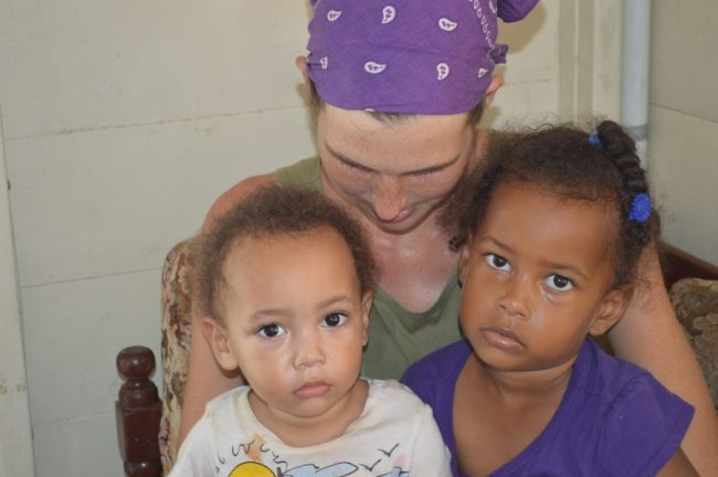 Amanda Gibson (centre), who has lost her partner Andre Hackett, holding their children Amarion (left) and Amiyah.