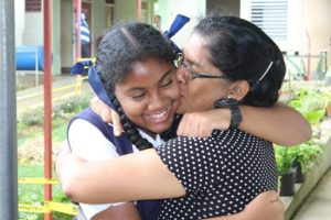 A happy Sarah Downes of Hillaby Turner's Hall Primary being congratulated by her mother Shameeza Bacchus.