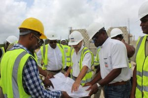 Representatives of Innotech Services Limited and other officials reviewing the plans for the police station and magistrates' Court under construction at Cane Garden in St Thomas.