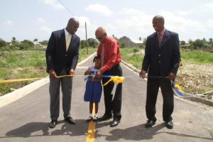 Five-year-old St Gabriel's student Chioma Hunte, granddaughter of Carl Springer, cuts the ribbon to declare the Carl Springer Drive open.