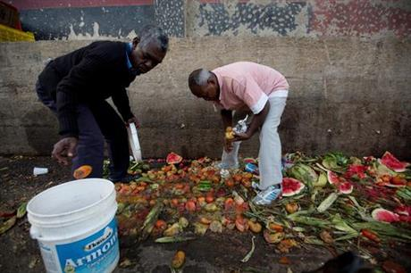 In this May 31, 2016 photo, Pedro Hernandez, left, and his friend Luis Daza, pick up tomatoes from the trash area of the Coche public market in Caracas, Venezuela.